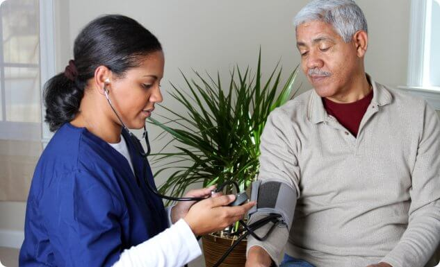 caregiver getting blood pressure of an adult man